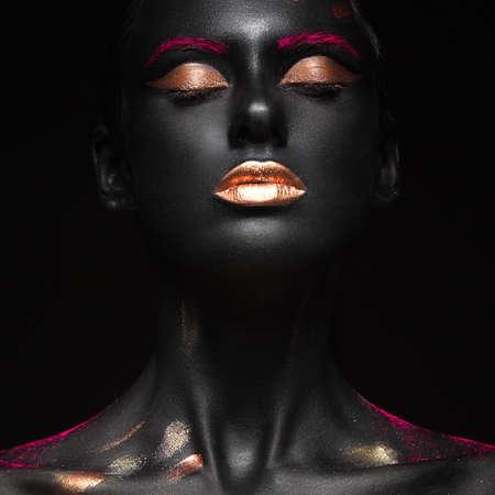 mode portret van een donkere huid meisje met kleur make-up.Beauty gezicht. Foto genomen in de studio op een zwarte achtergrond.