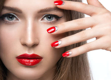 明るい化粧と赤い爪の美しい少女。白い背景のスタジオでの撮影。