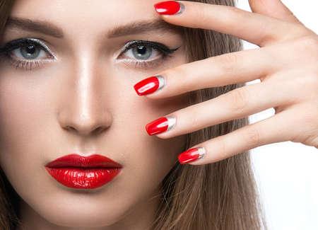 labios sensuales: Chica joven hermosa con un maquillaje brillante y las uñas rojas. Fotografía tomada en el estudio sobre un fondo blanco. Foto de archivo