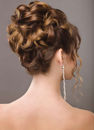 Portrait of a beautiful  woman in image of the bride. Picture taken in the studio on a black background. Beauty hair. Hairstyle back view