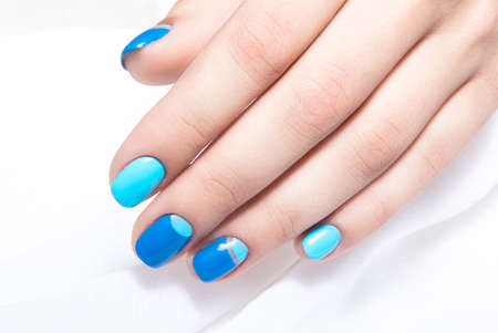Blue manicure in light and dark colors of lacquer on a white background. Nail art design