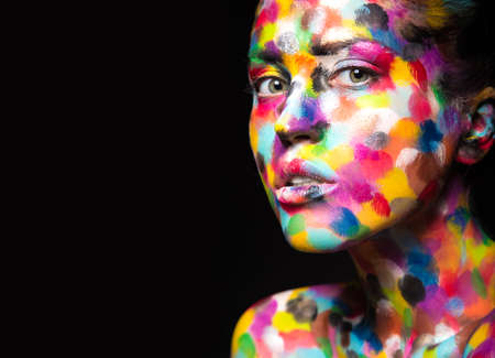 Girl with colored face painted. Art beauty image. Picture taken in the studio on a black background. Standard-Bild