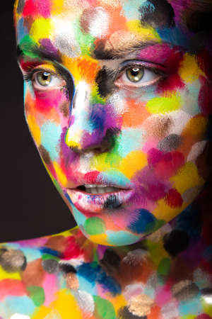 Girl with colored face painted. Art beauty image. Picture taken in the studio on a black background. Stok Fotoğraf