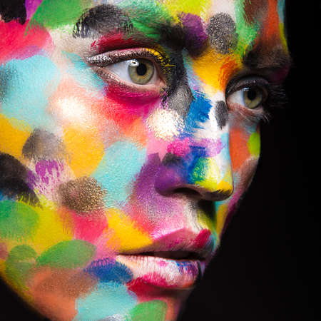 Girl with colored face painted. Art beauty image. Picture taken in the studio on a black background. Banque d'images