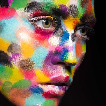 Muchacha con la cara pintada de color. Imagen Belleza Arte. Fotografía tomada en el estudio sobre un fondo negro.