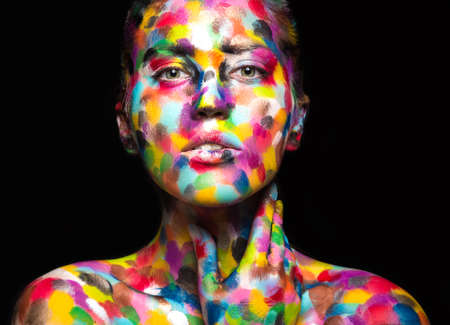 Girl with colored face painted. Art beauty image. Picture taken in the studio on a black background. 스톡 콘텐츠