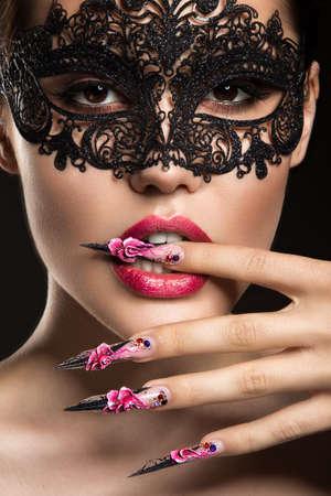 長い爪と官能的な唇を持つ美しい少女。肖像画は、黒の背景のスタジオで撮影。美容顔。