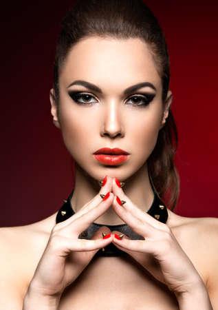 modelos desnudas: Mujer hermosa en estilo g�tico con maquillaje de noche y las u�as rojas con espinas. Fotograf�a tomada en un estudio sobre un fondo rojo.