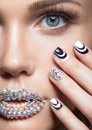 Beautiful girl with bright nails and lips of crystals, long eyelashes and curls. Beauty face. Picture taken in a studio. Stok Fotoğraf - 43879681