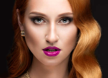 mujer elegante: Hermosa mujer de pelo rojo con maquillaje de la tarde, los labios rosados ??y rizos. Cara de la belleza. Fotograf�a tomada en el estudio sobre un fondo negro. Foto de archivo