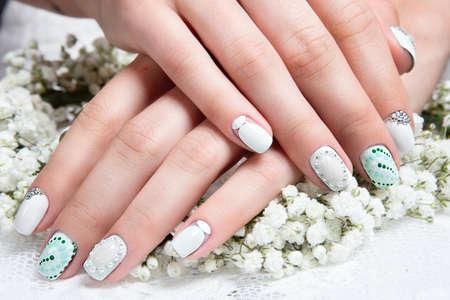 花を持つ穏やかなトーンの花嫁のための結婚式マニキュア。ネイル デザイン。 写真素材 - 44272069