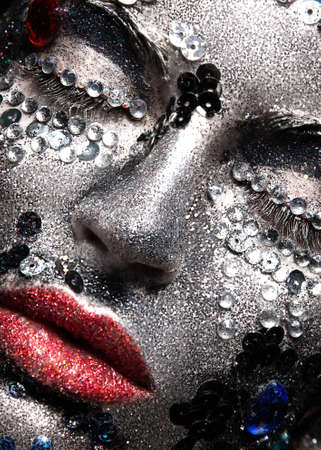 black makeup: Girl with glitter and rhinestones on her face. Beauty close-up. Picture taken in the studio.