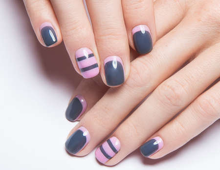 Beautiful womens manicure with gray and pink polish on the nails. Picture taken in the studio. Close-up.