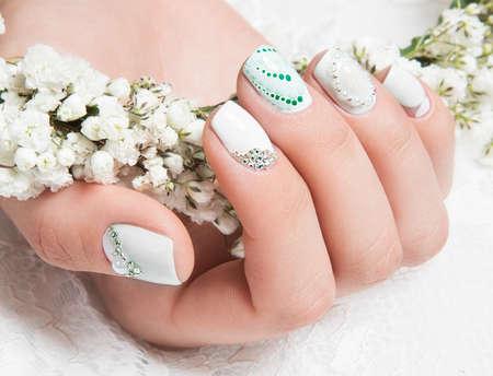 花を持つ穏やかなトーンの花嫁のための結婚式マニキュア。ネイル デザイン。