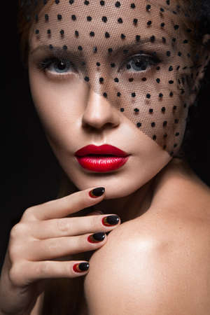 Beautiful girl with a veil, evening makeup, black and red nails. Design manicure. Beauty face. Picture taken in the studio. Standard-Bild