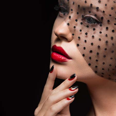 夜の化粧、黒と赤の爪、ベールを持つ美しい少女。マニキュアをデザインします。美容顔。スタジオでの撮影。 写真素材