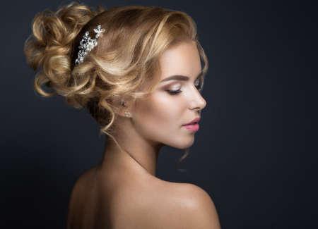 花嫁のイメージで美しい金髪の女性の肖像画。黒の背景にスタジオでの撮影。美容顔と髪型