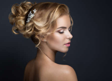 Portrait of a beautiful blond woman in the image of the bride. Picture taken in the studio on a black background. Beauty face and Hairstyle Standard-Bild