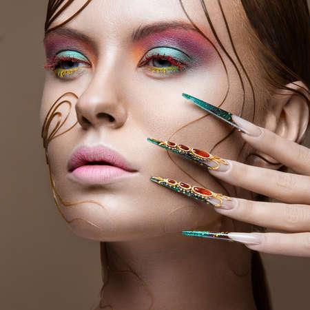 明るいファッション メイク、創造的な髪型、長い爪を持つ美しい少女。マニキュアをデザインします。美容顔。スタジオでの撮影。
