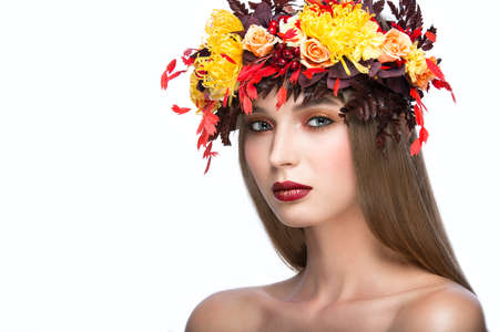 glamour: Beautiful girl with bright autumn wreath of leaves and flowers. Beauty face. Picture taken in the studio on a white background.