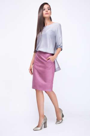 stile: Bella ragazza in vestiti alla moda alla moda, camminando su uno sfondo bianco. Foto scattata in studio. Bellezza, moda, stile.
