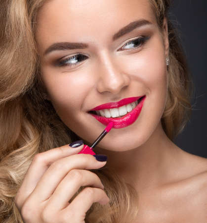 Beautiful blonde girl with curls, red lips and a smile on her face.  Picture taken in the studio. Stok Fotoğraf