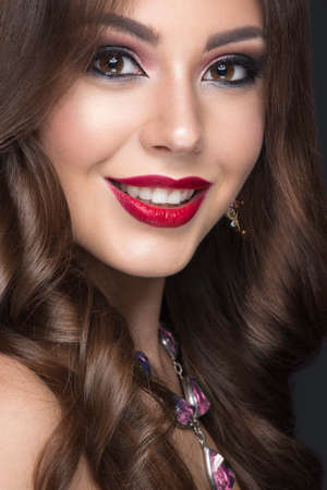 Beautiful woman with arabic make-up, red lips and curls. Beauty face. Picture taken in the studio on a gray background.