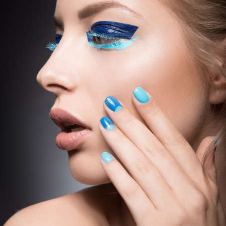 beautiful eye: Beautiful girl with bright creative fashion makeup and blue nail polish. Art beauty nail design. Picture taken in the studio.