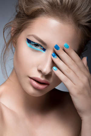 glitter makeup: Beautiful girl with bright creative fashion makeup and blue nail polish. Art beauty nail design. Picture taken in the studio.