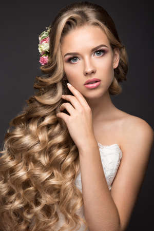 bride dress: Portrait of a beautiful blond woman in the image of the bride with flowers in her hair. Picture taken in the studio on a black background. Beauty face and Hairstyle