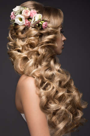 Portrait of a beautiful blond woman in the image of the bride with flowers in her hair. Picture taken in the studio on a black background. Beauty face and Hairstyle