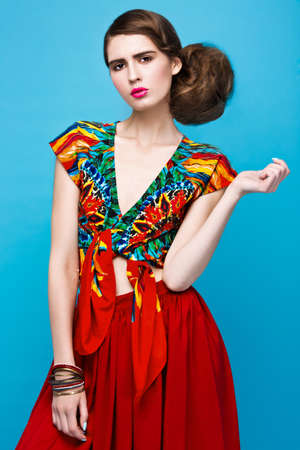 Beautiful fashionable woman an unusual hairstyle in bright clothes and colorful accessories. Cuban style. Picture taken in the studio on a bright background.