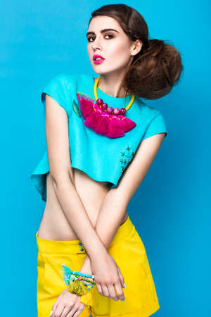 mooie vrouwen: Mooie modieuze vrouw een ongebruikelijk kapsel in lichte kleding en kleurrijke accessoires. Cubaanse stijl. Foto genomen in de studio op een lichte achtergrond. Stockfoto