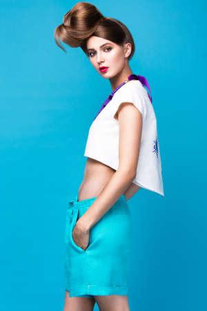 poses de modelos: Hermosa mujer de moda un peinado inusual en ropa brillante y accesorios de colores. Estilo cubano. Fotograf�a tomada en el estudio sobre un fondo brillante.