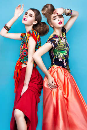 hairstyle: Beautiful fashionable women an unusual hairstyle in bright clothes and colorful accessories. Cuban style. Picture taken in the studio on a bright background. Stock Photo