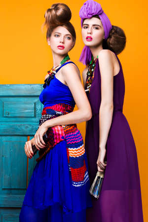 Beautiful fashionable women an unusual hairstyle in bright clothes and colorful accessories. Cuban style. Picture taken in the studio on a bright background. Standard-Bild