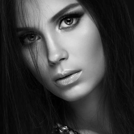 Beautiful woman with evening make-up and long straight hair . Smoky eyes. Fashion photo. Picture taken in the studio on a black  background. Black and white photo