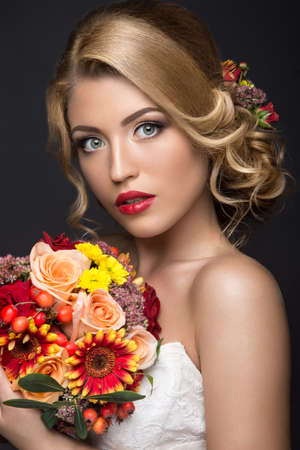 glamour makeup: Portrait of a beautiful blond woman in the image of the bride with flowers in her hair. Picture taken in the studio on a black background. Beauty face and Hairstyle
