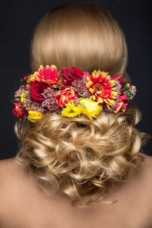 wedding hairstyle: Portrait of a beautiful blond woman in the image of the bride with flowers in her hair. Picture taken in the studio on a black background. Beauty face and Hairstyle back view Stock Photo