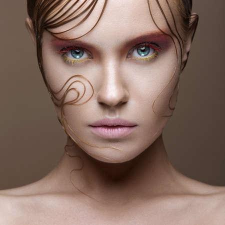 ragazza innamorata: Bella ragazza con il trucco luminoso e colorato ciocche bagnate di capelli sul viso. Immagine creativa. Foto scattata in studio.