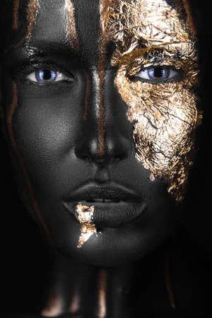 ファッションは金メイクアップと浅黒い肌の少女の肖像画。美容顔。黒の背景にスタジオでの撮影。 写真素材
