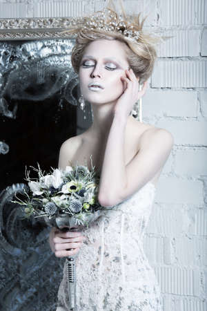 ice queen: Beautiful girl in white dress in the image of the Snow Queen with a crown on her head. Picture taken in the studio with decorations.
