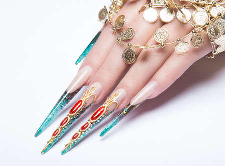 Long beautiful manicure on the fingers of turquoise and red. Nails design. Picture taken in the studio on a white background. Isolate object.