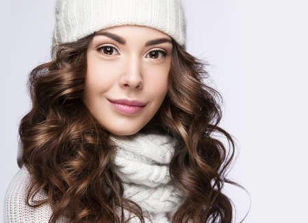 mujer elegante: Hermosa chica con un suave maquillaje, rizos y una sonrisa en invierno gorro de lana blanca. Imagen Invierno cálido. Cara de la belleza. Fotografía tomada en el estudio.