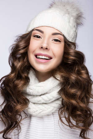 knit cap: Beautiful girl with a gentle make-up, curls and a smile in winter white knit cap. Warm winter image. Beauty face. Picture taken in the studio.