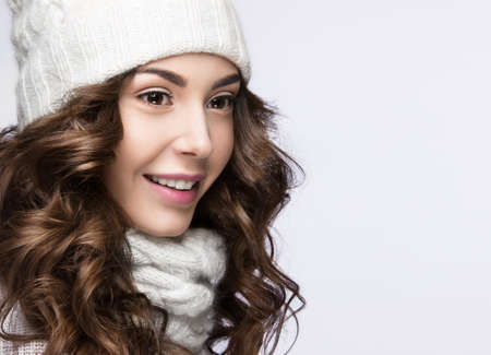 image style: Beautiful girl with a gentle make-up, curls and a smile in winter white knit cap. Warm winter image. Beauty face. Picture taken in the studio.