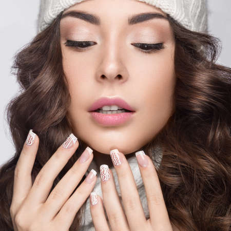 fall winter: Beautiful girl with a gentle make-up, design manicure and a smile in winter white knit cap. Warm winter image. Beauty face. Picture taken in the studio.