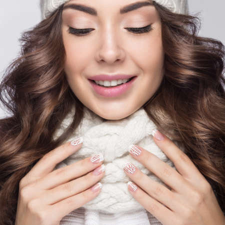 Beautiful girl with a gentle make-up, design manicure and a smile in winter white knit cap. Warm winter image. Beauty face. Picture taken in the studio.