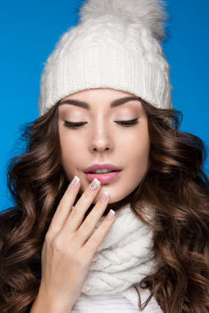 elegant girl: Beautiful girl with a gentle make-up, design manicure and a smile in winter white knit cap. Warm winter image. Beauty face. Picture taken in the studio.