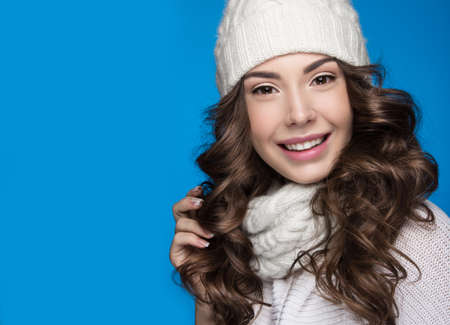 winter fashion: Beautiful girl with a gentle make-up, design manicure and a smile in winter white knit cap. Warm winter image. Beauty face. Picture taken in the studio.